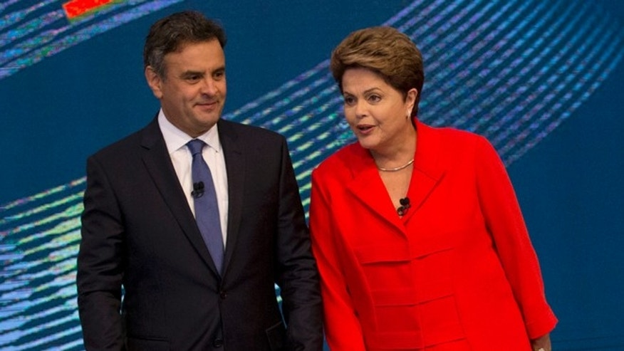 Brazil's incumbent President and Workers Party presidential candidate Dilma Rousseff, right, and challenger Aecio Neves, presidential candidate of the Brazilian Social Democracy Party, arrive on stage for the start of their presidential debate, in Rio de Janeiro, Brazil, Friday, Oct. 24, 2014. Rousseff and Neves are in a tight election contest, that culminates Sunday when millions of Brazilians are expected to go to the polls and decide who'll be the next leader of Latin America's biggest economy. (AP Photo/Silvia Izquierdo)