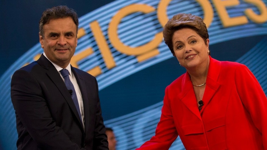 Brazil's incumbent President and Workers Party presidential candidate Dilma Rousseff, right, and challenger Aecio Neves, presidential candidate of the Brazilian Social Democracy Party, shake hands at the start of their presidential debate, in Rio de Janeiro, Brazil, Friday, Oct. 24, 2014. Rousseff and Neves are in a tight election contest, that culminates Sunday when millions of Brazilians are expected to go to the polls and decide who'll be the next leader of Latin America's biggest economy. (AP Photo/Silvia Izquierdo)