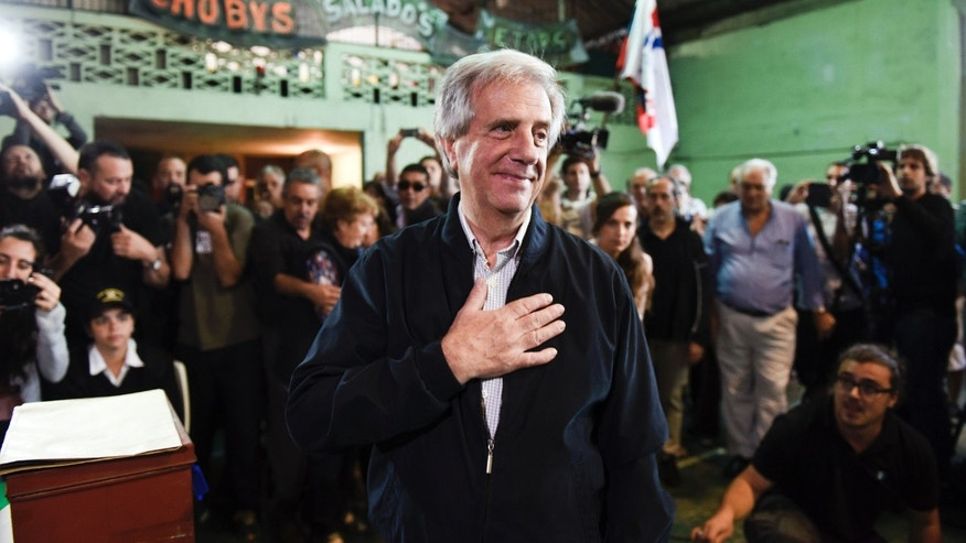 Presidential candidate for the ruling Front Broad party Tabare  Vazquez holds his hand over his chest after casting his vote in the general elections, in Montevideo, Uruguay, Sunday, Oct. 26, 2014. Exit polls in Uruguay say left-leaning candidate Tabare Vazquez won the most votes in Sundayâs presidential election, but he fell short of the outright majority needed to avoid a Nov. 30 runoff. (AP Photo/Matilde Campodonico)