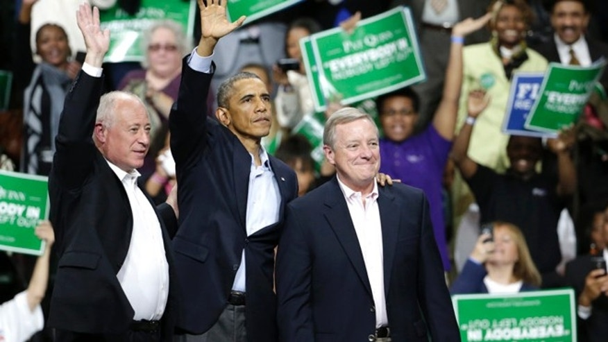 In this Sunday, Oct. 9, 2014 photo, President Barack Obama, center, stands with Illinois Gov. Pat Quinn, left, and U.S. Sen. Dick Durbin, during an early voting and campaign rally for Illinois Gov. Pat Quinn at Chicago State University Sunday in Chicago.
