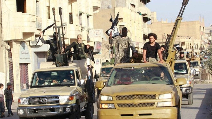 In this June 30, 2014 photo, militant Islamist fighters in military vehicles parade along the streets of Syria's northern Raqqa province.