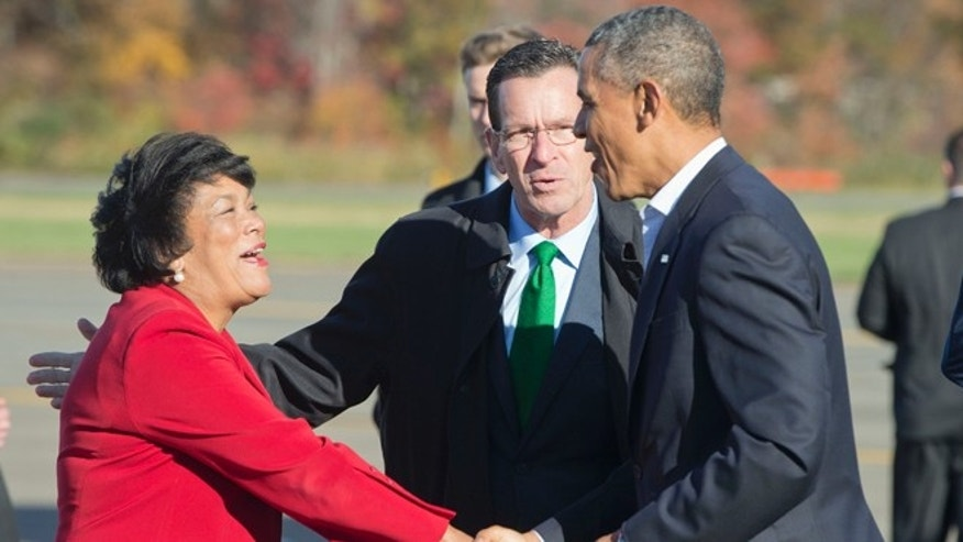 President Obama, right, is greeted by Gov. Dan Malloy, center, and New Haven Mayor Toni Harp, at Tweed New Haven Airport, in Connecticut.