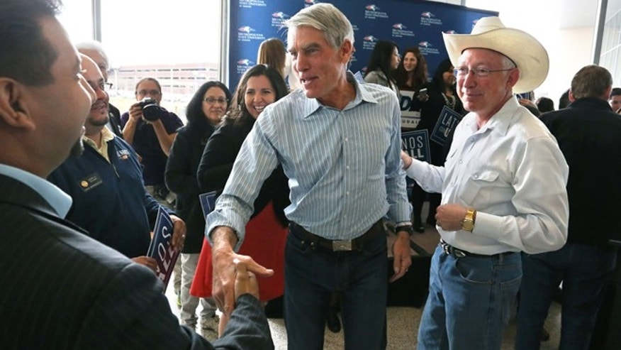 U.S. Sen. Mark Udall, center, flanked by former U.S. Secretary of the Interior Ken Salazar, right, greets supporters during a campaign stop focusing on Latino-American issues, at Metro State University, in Denver, Monday, Nov. 3, 2014. Democratic Sen. Mark Udall is in the fight of his political life as he tries to stave off the Republican challenger U.S. Rep. Cory Gardner in a race that is seen as key to both control of the U.S. Senate and questions about the GOP's national viability. (AP Photo/Brennan Linsley)