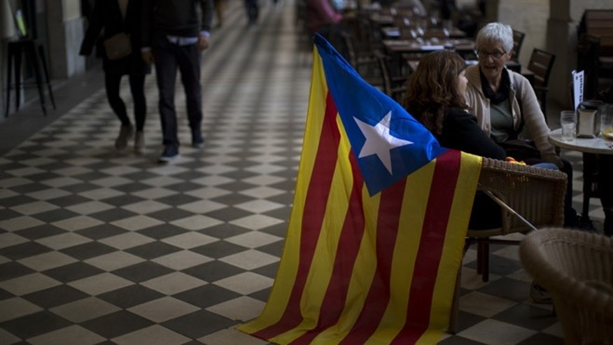 People sit in a restaurant ahead of an informal poll scheduled for next Sunday is seen in a street in Girona, Spain, on Saturday Nov.8, 2014. The pro-independence regional government of Catalonia stages a symbolic poll on secession in a show of determination and defiance after the Constitutional Court suspended its plans to hold an official independence referendum following a legal challenge by the Spanish government. (AP Photo/Emilio Morenatti)