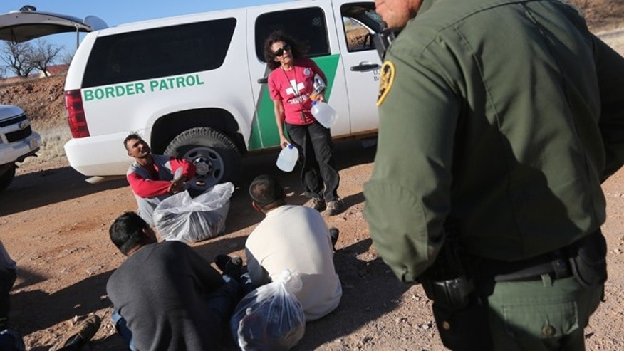 U.S. Border Patrol agents guard a group of Mexican immigrants caught after they crossed illegally into the United States on March 6, 2013 near Walker Canyon, Arizona.(Photo by John Moore/Getty Images)