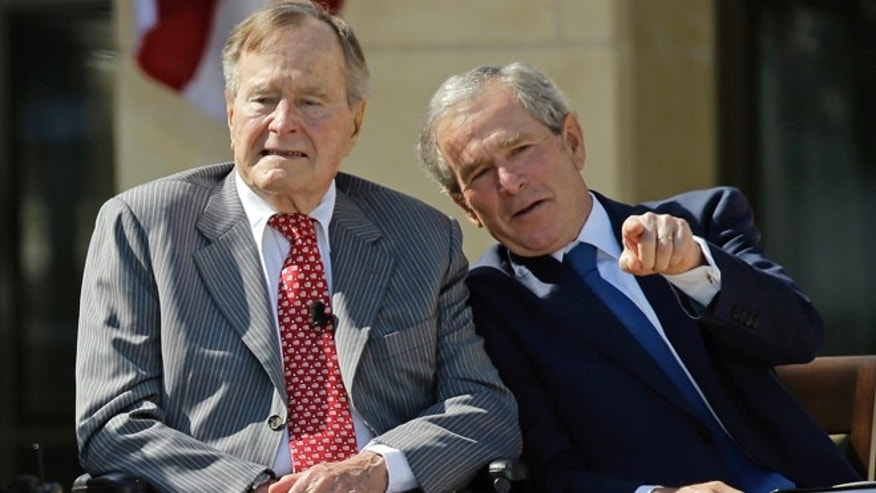 April 25, 2013: Former President George W. Bush talks with his father, former President George H. W. Bush, left, during the dedication of the George W. Bush Presidential Center in Dallas.
