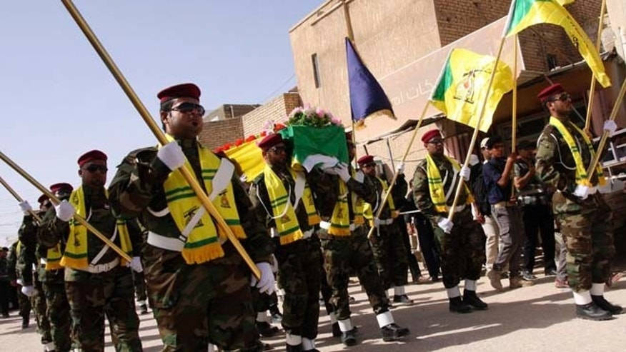 In this June 5, 2013 photos, members of Hezbollah Iraq march during a funeral in Kerbala, 70 miles south of Baghdad.