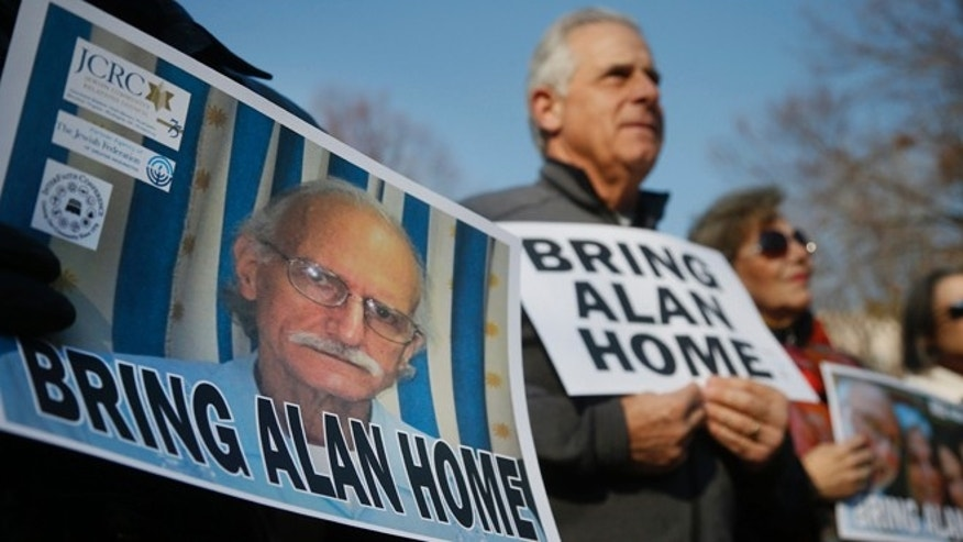 FILE - In this Dec. 3, 2013 file photo, supporters of Alan Gross, on poster at left, mark his fourth year in a Cuban prison with a protest in Lafayette Park, across from the White House in Washington D.C. Two U.S. senators said Tuesday, Nov. 11, 2014 that theyâre optimistic that the imprisoned American government contractor will be freed. Sens. Jeff Flake of Arizona and Tom Udall of New Mexico said in Havana that they met Gross for about two hours during a trip that included meetings with Cuban officials. Gross was detained in December 2009 while working to set up Internet access as a subcontractor for the U.S. government's U.S. Agency for International Development. He was tried and sentenced to 15 years in prison. (AP Photo/Charles Dharapak, File)