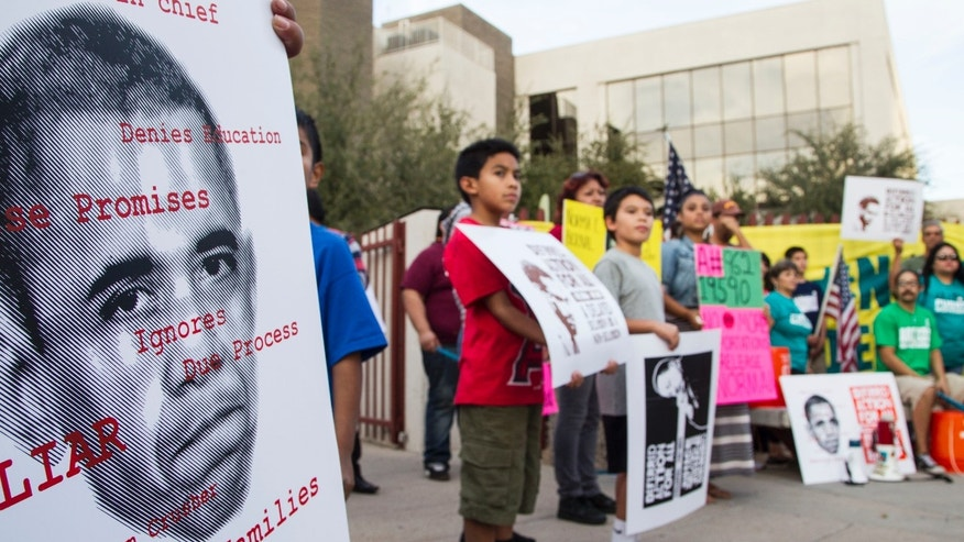 The activist group Puente, accompanied by family and friends facing deportation, holds a rally for deferred action for undocumented immigrants outside the U.S. Immigration and Customs Enforcement office in Phoenix on Friday, Nov. 13, 2014. (AP Photo/The Arizona Republic, Nick Oza)
