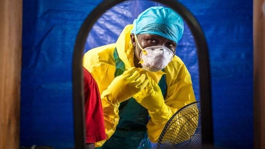 In this Thursday, Oct. 16, 2014 file photo, a healthcare worker dons protective gear before entering an Ebola treatment center in the west of Freetown, Sierra Leone.