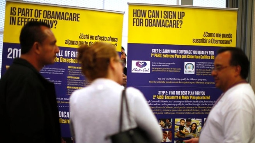 Mar. 31. 2014: Julian Gomez (R) explains Obamacare to people at a health insurance enrolment event in Commerce, California. (Reuters)