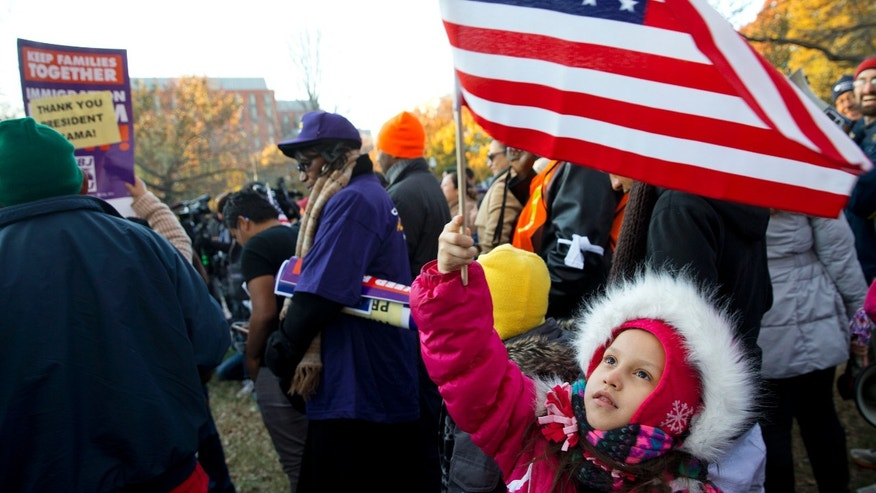 Nov. 21, 2014: Joselyn Vargas, 7, of Hyattsville, Md., waves a U.S. flag during a rally in Lafayette Park across from the White House in Washington