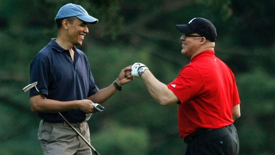In this April 23, 2010 file photo, President Obama plays golf with Eric Whitaker at the Grove Park Inn Resort in Asheville, North Carolina.