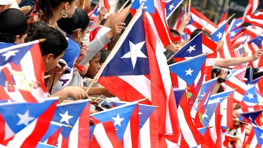 File Photo: People look downtown toward the oncoming parade amonbst a sea of Puerto Rican Flags  during the Puerto Rican Day parade, June 8, 2003 in New York City. Thousands lined Fifth Avenus to watch the parade which stretched over 40 blocks.(Photo by Stephen Chernin/Getty Images)