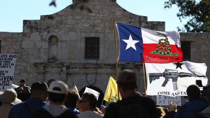 "Oct. 19, 2013: In this file photo, flags fly at the ""Come And Take It San Antonio"" rally. Long depicted as the rootin'-tootin' capital of American gun culture, Texas is one of the few states with an outright ban on the open carry of handguns. That could change next year, with an expected push for expanding gun rights from the Republican-dominated Legislature."