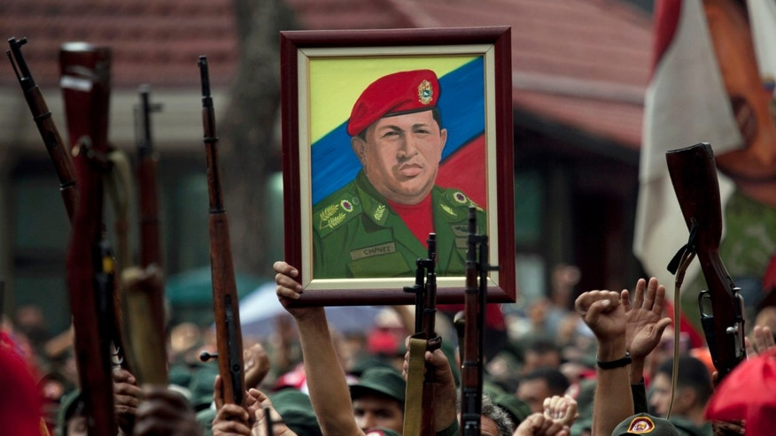 FILE - In this April 13, 2010 file photo, members of the National Revolutionary Militia hold up their weapons and a painting of Venezuela's President Hugo Chavez at an event marking the 9th anniversary of Chavez's return to power after a failed 2002 coup, in Caracas, Venezuela. Venezuela has found yet another way to honor the late leader who launched Venezuela's socialist revolution. A state-sponsored ballet about his life premieres on Saturday, Nov. 29, 2014, with dozens of performers recounting Chavez's life, from humble roots, to failed coup, to international fame. (AP Photo/Ariana Cubillos, File)