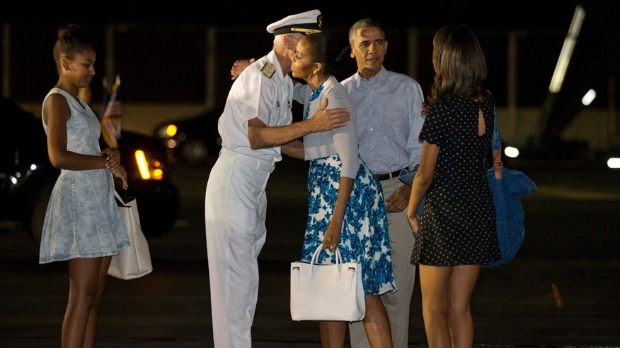 Dec. 20, 2014: First lady Michelle Obama hugs Admiral Samuel Locklear III, Commander, U.S. Pacific Command, with daughter Sasha Obama, left, and Malia Obama, far right, and President Barack Obama as the first family arrives at Pearl Harbor