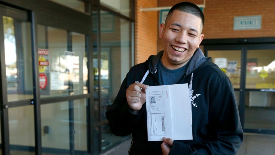 Ramon Maldonado, of Phoenix, smiles as he holds up his new temporary Arizona driver's license after passing the required tests as he leaves the Arizona Department of Transportation Motor Vehicle Division office, Monday, Dec. 22, 2014, in Phoenix. Monday marked the first day that about 20,000 immigrants in the country illegally who have received protection from deportation could apply for Arizona licenses. (AP Photo/Ross D. Franklin)