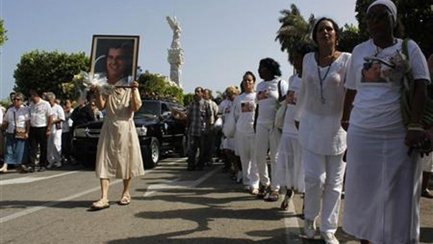 July 24, 2012: Members of the 'Ladies in White' opposition group march beside the funeral procession of Oswaldo Paya, one of Cuba's best-known dissidents, in Havana. (Reuters/File)