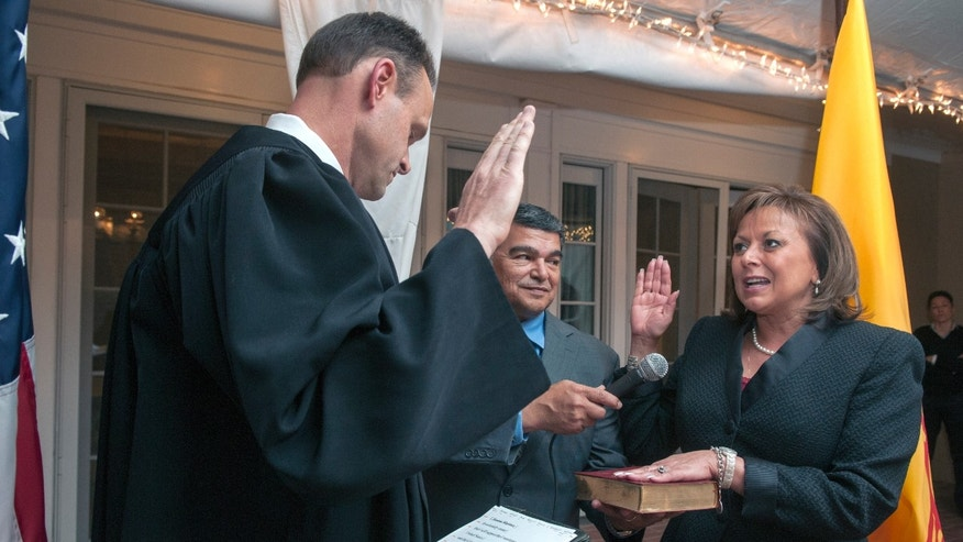 New Mexico Court of Appeals Judge Miles Hanisee, left, administers the oath of office to Gov. Susana Martinez, right, with first gentleman Chuck Franco, center, holding the Bible, in a private ceremony at the Governor's Manson in Santa Fe, N.M., on Thursday Jan. 1, 2015. Martinez started her second term as governor at midnight. (AP Photo/Albuquerque Journal, Eddie Moore, Pool)