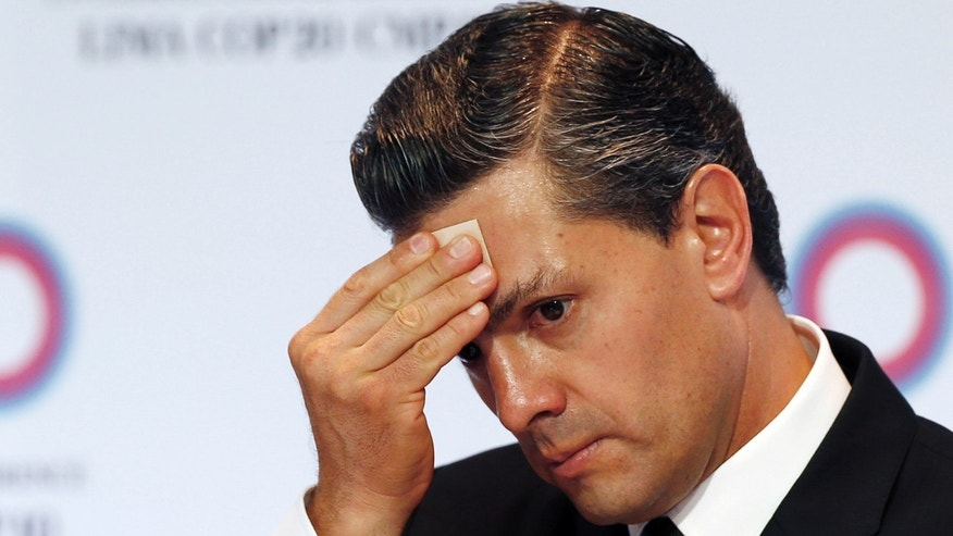 FILE - In this Dec. 10, 2014 file photo, Mexico's President Enrique Pena Nieto wipes sweat from his brow during a signing ceremony among the Pacific Alliance at the Climate Change Conference in Lima, Peru. The Mexican president and his team started 2014 carrying out a slew of newly passed reforms earning him international plaudits. Then came a 1-2-3 punch of scandals: Soldiers killing 22 civilians in a questionable shootout; the abduction and presumed murder of 43 college students, allegedly at the hands of local officials and police in league with a drug cartel; and revelations that Pena Nieto and his treasury secretary live in luxury homes built and financed by a favorite government contractor. (AP Photo/Juan Karita, File)