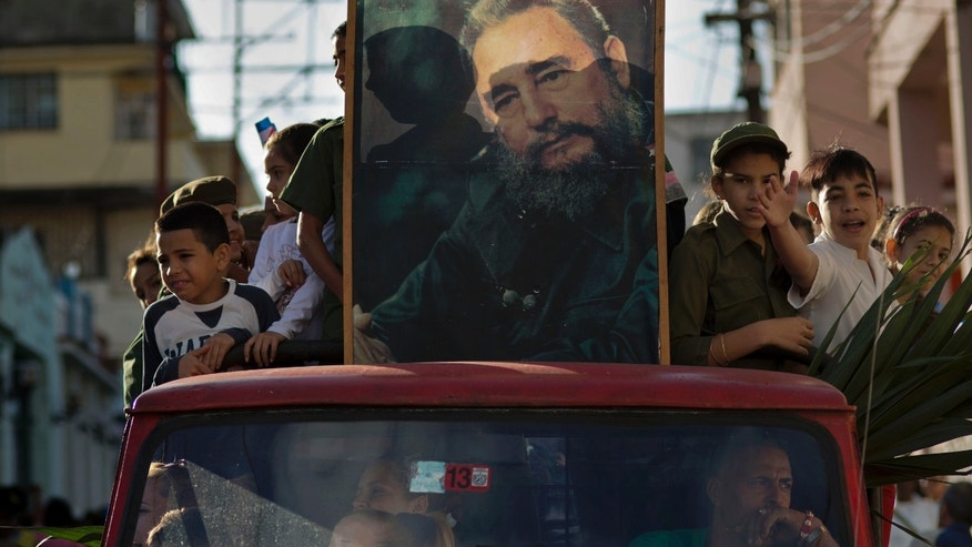 Children ride in the bed of a truck with a framed image of Fidel Castro, in Regla, Cuba, Thursday, Jan. 8, 2015.