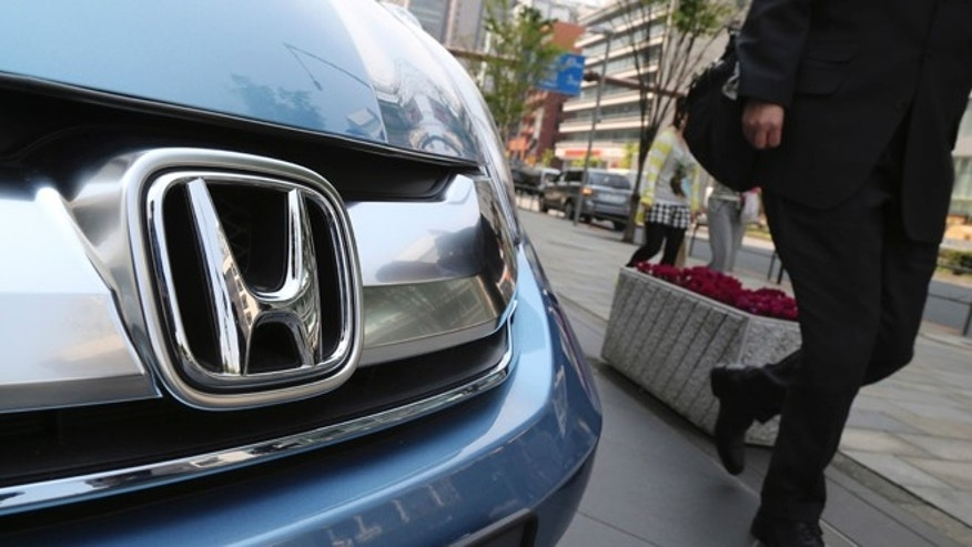 In this April 25, 2014 file photo, a man walks past a Honda on display at Honda Motor Co. headquarters in Tokyo.