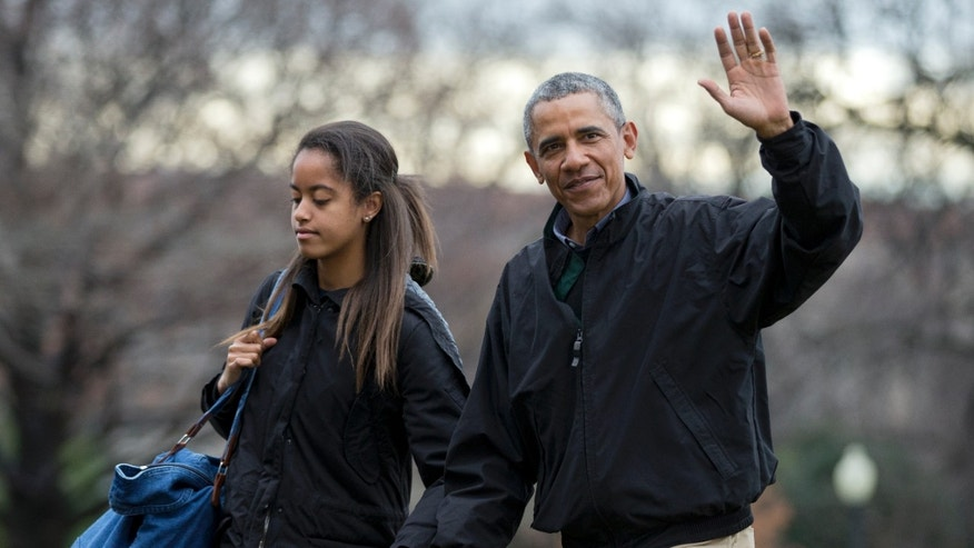 Jan. 4, 2015: President Barack Obama, right, with his daughter Malia Obama, waves as they arrive at the White House in Washington.