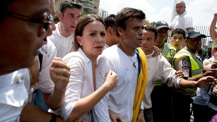 Venezuelan congresswoman Maria Corina Machado, left, and opposition leader Leopoldo Lopez, center, are surrounded by anti-government demonstrators before Lopez surrenders to national guards, in Caracas, Venezuela, Tuesday, Feb 18, 2014. Lopez re-emerged from days of hiding to address an anti-government demonstration and then surrendered to authorities Tuesday in a move that he said will open the world's eyes to the increasingly authoritarian bent of Venezuela's socialist government.(AP Photo/Juan Manuel Hernandez)