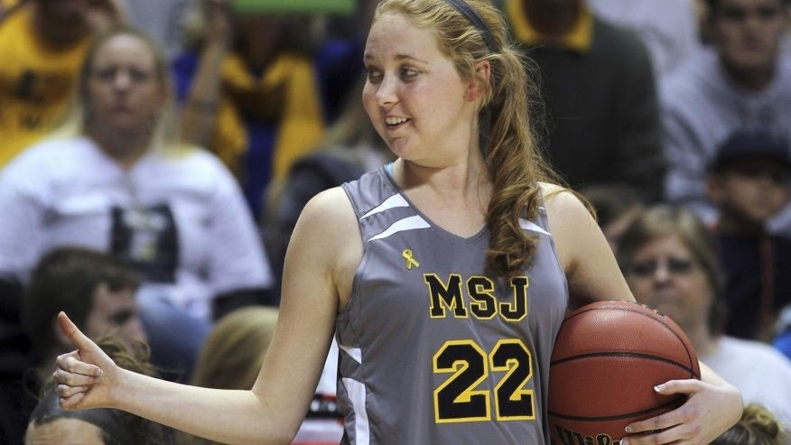 Nov. 2, 2014: In this file photo, Mount St. Joseph's Lauren Hill gives a thumbs-up as she holds the game ball during her first NCAA college basketball game against Hiram University at Xavier University in Cincinnati.