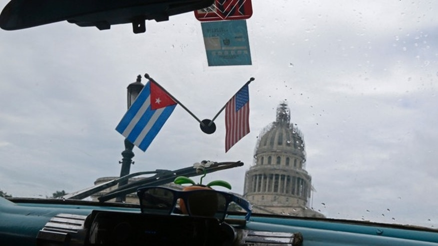 A Cuban and U.S. miniature national flags decorate the inside of a classic American car used as a collective taxi passes the Capitol Building in Havana, Cuba, Friday, Jan. 16, 2015. Tens of thousands more American tourists are expected to flock this year to a country where some five-star hotels don't have working air-conditioning or hand towels. The Obama administration hopes the new wave of U.S. tourists will fuel one of the healthiest parts of Cuba's new entrepreneurial sector, the thousands of private bed and breakfasts. (AP Photo/Desmond Boylan)