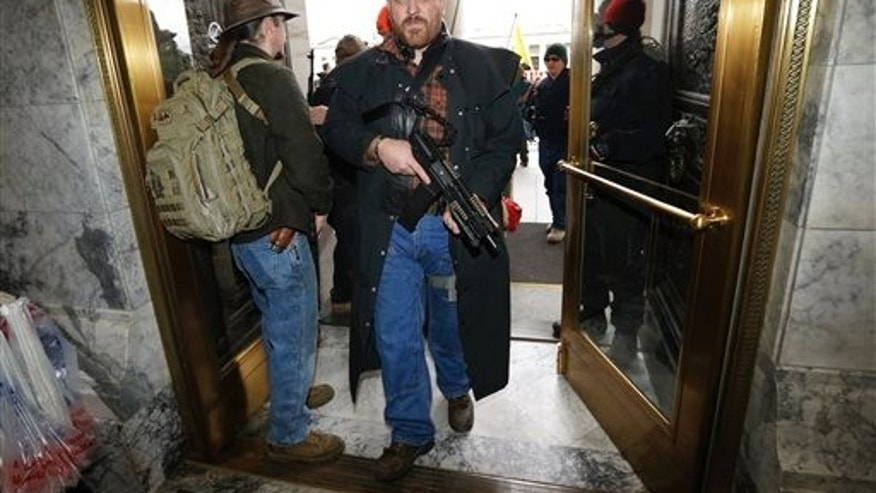 Jason McMillon carries his Rock River LAR-PDS pistol with a 45-round magazine into the Legislative Building at the Capitol in Olympia, Wash., Thursday, Jan. 15, 2015, during a gun-rights rally opposing the state's Initiative 594, which requires - with only a few exceptions - background checks on all gun sales and transfers. Rules at the Capitol allow guns to be carried openly in the building. (AP Photo/Ted S. Warren)