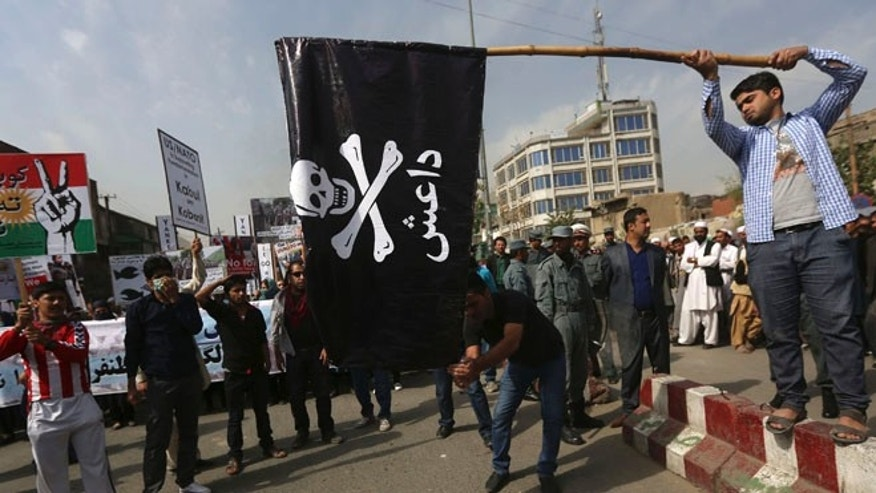 FILE: Oct. 12, 2014: Men prepare to set fire to an Islamic State flag during a protest in Kabul, Afghanistan.