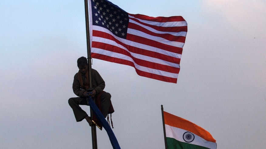 Jan. 23, 2015: An Indian worker places an American flag on a flag pole in New Delhi, India.