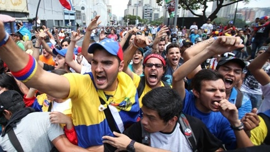 Opposition students shouts slogans against supporters of Venezuela's late President Hugo Chavez during a protest a few blocks from the electoral commission in Caracas, Venezuela, Thursday, March 21, 2013.  The students were asking that the commission eliminate requirements that voters have their fingerprints recorded before voting. They were also demanding the government not interfere in politics ahead of an April 14 vote to replace Chavez. (AP Photo/Fernando Llano)