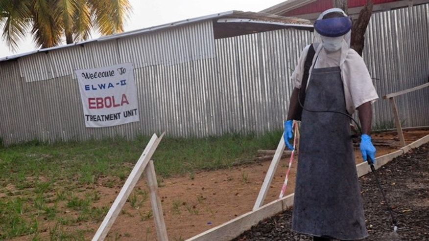 Jan. 30, 2015: A health care worker sprays disinfectant outside a USAID-funded Ebola clinic in Monrovia, Liberia.