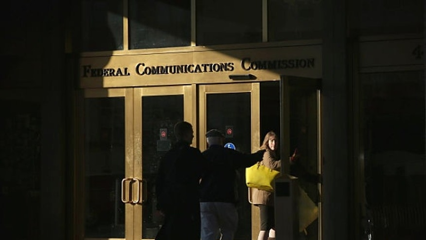 WASHINGTON, DC - DECEMBER 11:  People enter the building of Federal Communications Commission December 11, 2014 in Washington, DC. The commission held its monthly meeting as activists held a rally outside to call for net neutrality.  (Photo by Alex Wong/Getty Images)
