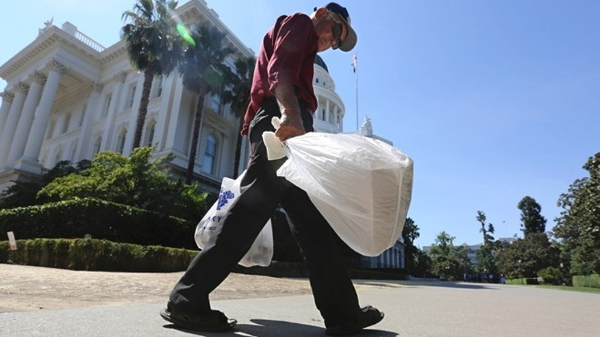 Aug. 12, 2014: File photo, a man carries plastic single-use bags past the State Capitol in Sacramento, Calif.