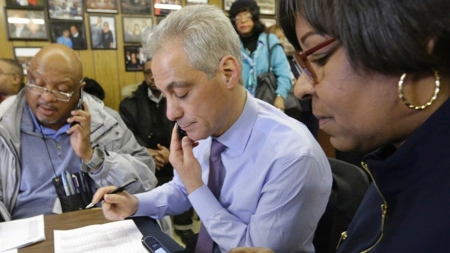 Feb. 24, 2015: Chicago Mayor Rahm Emanuel, center, and 8th ward Alderman Michelle Harris, right, join phone bank workers on election day in Chicago. (AP)