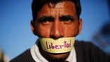 """A protester with his mouth covered with a piece of tape that reads in Spanish: """"freedom"""" attends a demonstration demanding the release of Metropolitan Mayor Antonio Ledezma in Caracas, Venezuela, Friday, Feb. 20, 2015. Demonstrators are condemning last night's surprise arrest of the Caracas' mayor for allegedly plotting to overthrow the government of President Nicolas Maduro. Late Thursday Maduro said that Ledezma, one of the most vocal opposition leaders, would be punished for trying to sow unrest in Venezuela. (AP Photo/Ariana Cubillos)"""