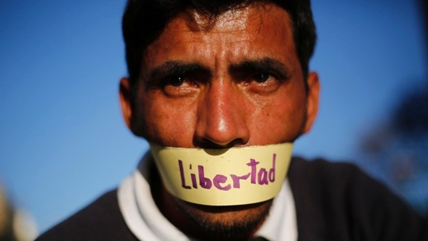 "A protester with his mouth covered with a piece of tape that reads in Spanish: ""freedom"" attends a demonstration demanding the release of Metropolitan Mayor Antonio Ledezma in Caracas, Venezuela, Friday, Feb. 20, 2015. Demonstrators are condemning last night's surprise arrest of the Caracas' mayor for allegedly plotting to overthrow the government of President Nicolas Maduro. Late Thursday Maduro said that Ledezma, one of the most vocal opposition leaders, would be punished for trying to sow unrest in Venezuela. (AP Photo/Ariana Cubillos)"