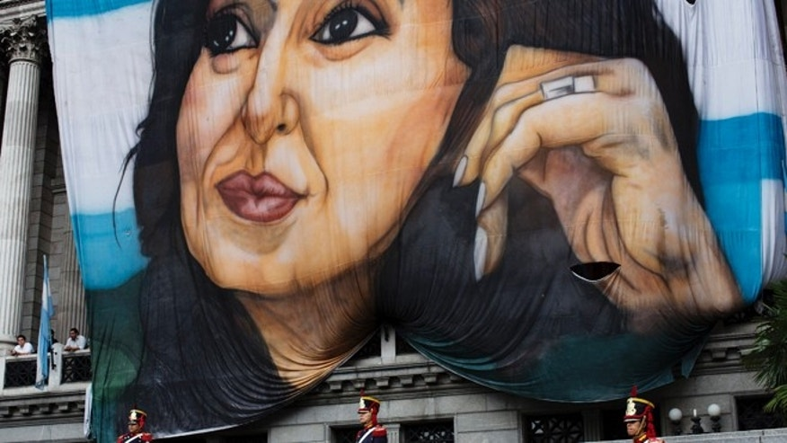 Soldiers of the Granaderos de San Martin regiment stand guard below a giant portrait of Argentina's President Cristina Fernandez hanging outside Congress during the inauguration of the 2015 legislative year in Buenos Aires, Argentina, Sunday, March 1, 2015. In her speech to Congress, Fernandez said prosecutor Alberto Nisman, who had accused her of a criminal cover-up, had also praised her. Nisman was found dead Jan. 18, hours before he was to meet legislators to elaborate on his allegations. (AP Photo/Rodrigo Abd)