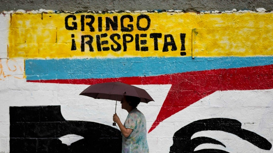 "A woman using an umbrella during a drizzle walks by a mural representing the eyes of Venezuela's independence hero Simon Bolivar that reads in Spanish ""Gringo, respect!"" in Caracas, Venezuela, Monday, March 2, 2015. Venezuelaâs government has given the U.S. two weeks to slash the size of its mission here to 17 diplomats as tensions between the two nations rise. (AP Photo/Ariana Cubillos)"