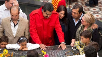 Venezuela's President Nicolas Maduro places his hands on the tomb of Venezuela's late President Hugo Chavez as he gathers with Chavez's family and government officials to mark the second anniversary of Chavez's death inside the 4F military museum in Caracas, Venezuela, Thursday, March 5, 2015. To the right of Maduro are first lady Cilia Flores, and Chavez's brother Adan. Chavez died of cancer at age 58 on March 5, 2013. (AP Photo/Ariana Cubillos)