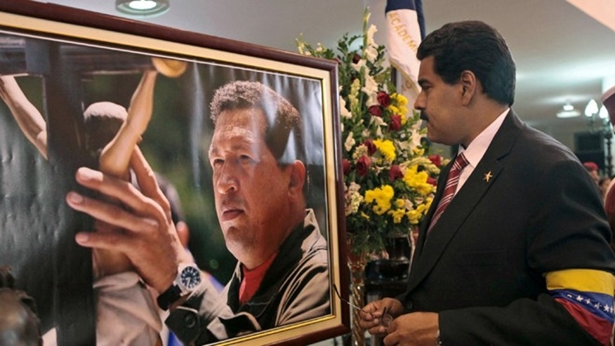 FILE -March 8, 2013 file photo released by Miraflores Press Office: Venezuela's President Nicolas Maduro stands in front of a portrait of Venezuela's late President Hugo Chavez. (AP Photo/Miraflores Press Office, File)