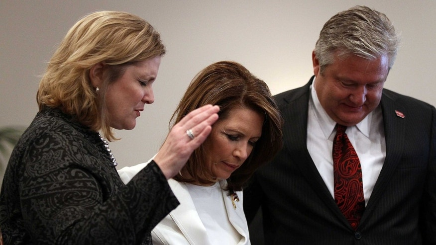 OSKALOOSA, IA - JANUARY 01:  Republican presidential candidate Rep. Michele Bachmann (R-MN) (C) and her husband Marcus pray from the pulpit while attending services at the Jubilee Family Church January 1, 2012 in Oskaloosa, Iowa. Bachmann also delivered personal testimony during the service as GOP presidential contenders are crisscrossing Iowa in the final stretch of campaigning before the January 3rd caucus, the first test the candidates must face before becomi  (Photo by Win McNamee/Getty Images)