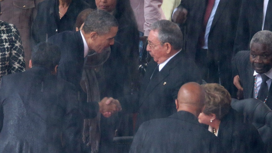 President Obama shakes hands with Cuban President Raul Castro on December 10, 2013 in Johannesburg, South Africa.