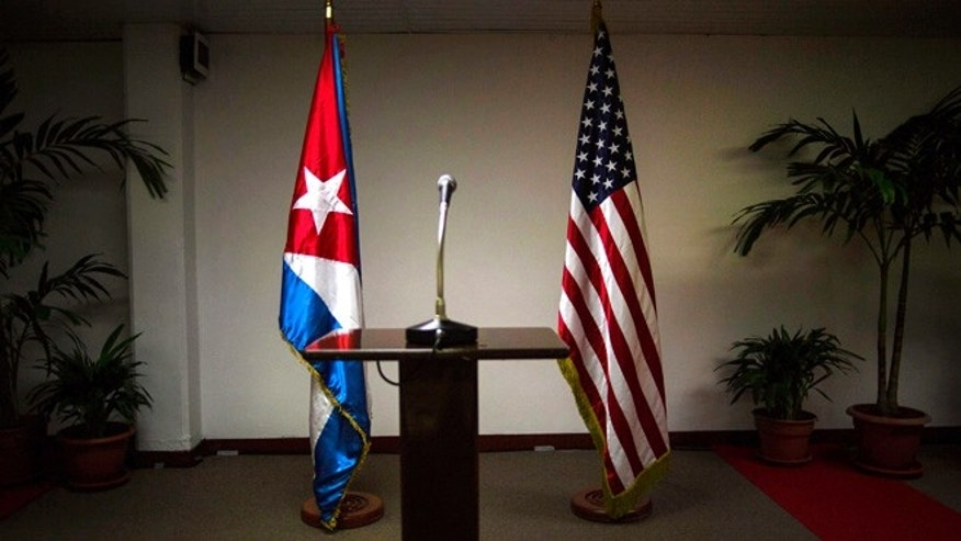FILE - In this Jan. 22, 2015 file photo, a Cuban and U.S. flag stand before the start of a press conference on the sidelines of talks between the two nations in Havana, Cuba. The U.S. hopes to open an embassy in Havana before presidents Barack Obama and Raul Castro meet at a regional summit in April, which will be the scene of the presidentsâ first face-to-face meeting since they announced on Dec. 17 that they will re-establish diplomatic relations after a half-century of hostility. (AP Photo/Ramon Espinosa, File)