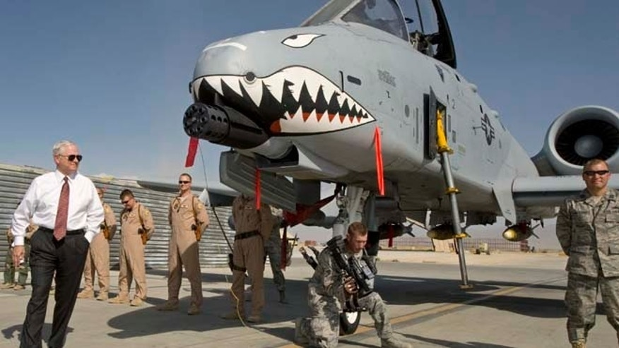 "FILE 2008: Then-US Secretary of Defense Robert Gates, left, greets the crew and looks over an A-10 ""Warthog,"" a close support aircraft, during an unannounced visit to Bagram Airfield."
