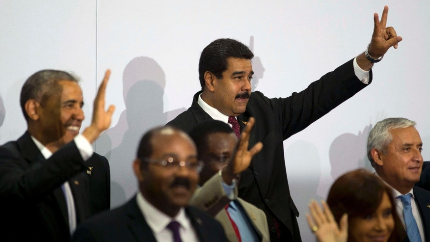 April 11, 2015: Venezuela's President Nicolas Maduro, center top, flashes a sign during the VII Summit of the Americas' official group photo in Panama City, Panama.